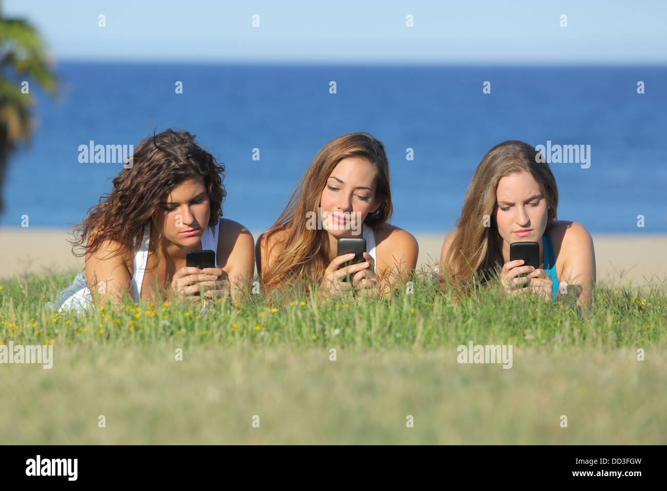 Group of three teenager girls typing on the mobile phone lying on the grass with the sea in the background - Stock Image
