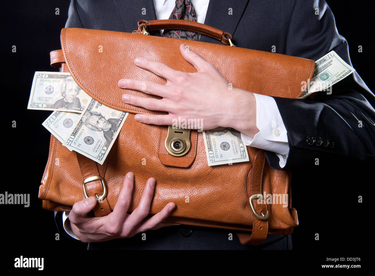 Closeup of man holding briefcase with money spilling out close to his chest - Stock Image