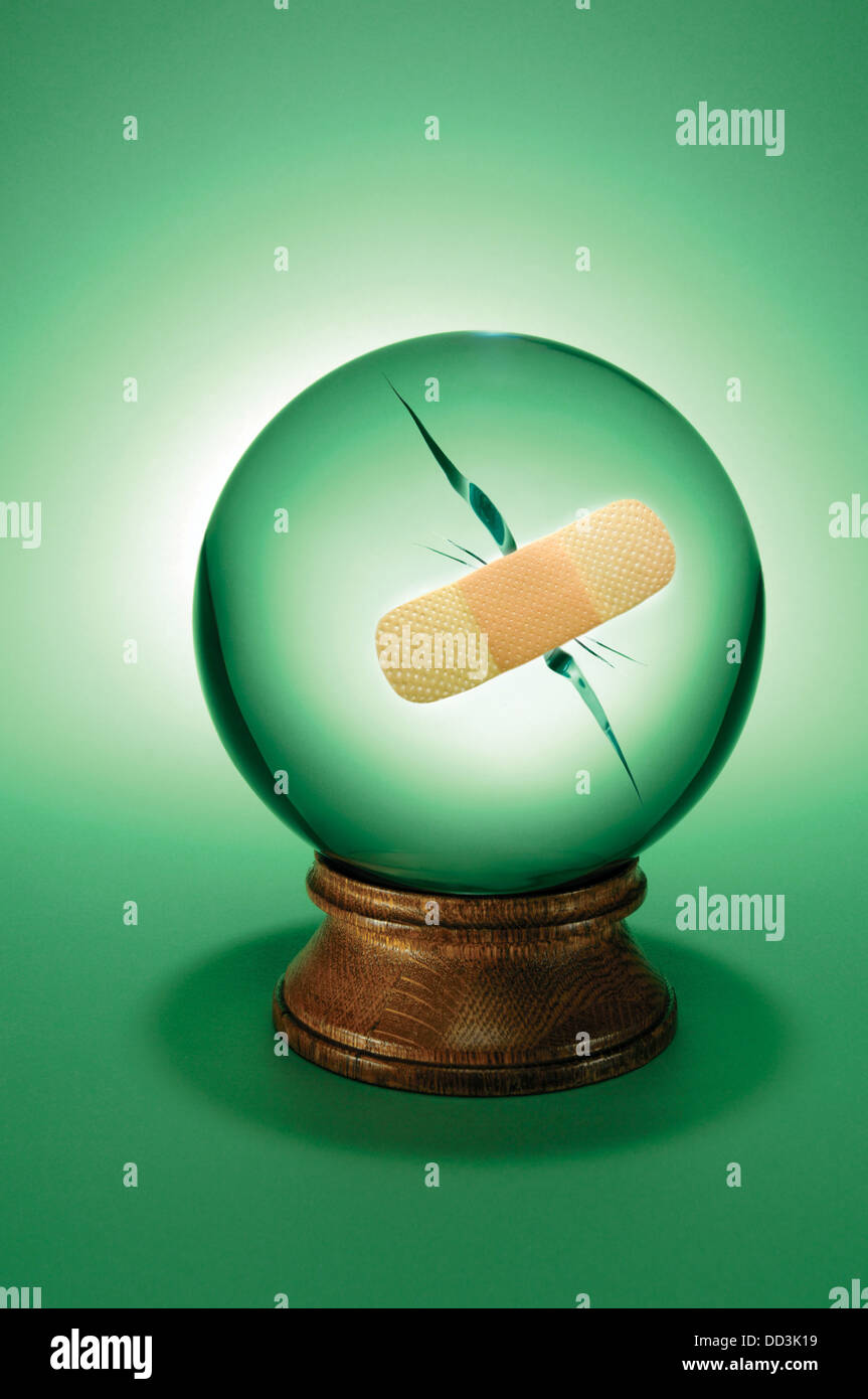 A large crystal ball with a large crack in it. A band-aid bandage has been applied - Stock Image