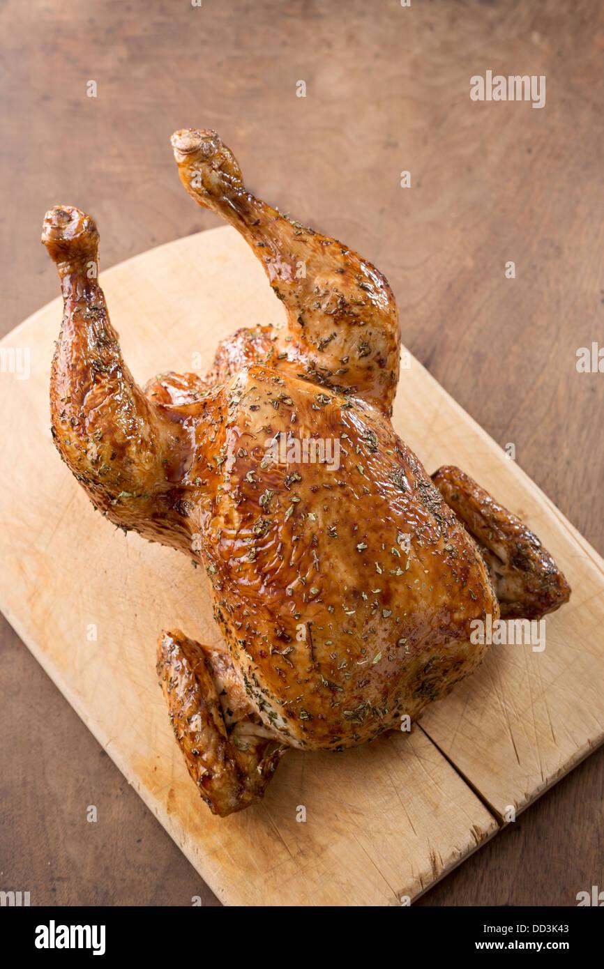 Whole roast chicken on wooden table overlook - Stock Image