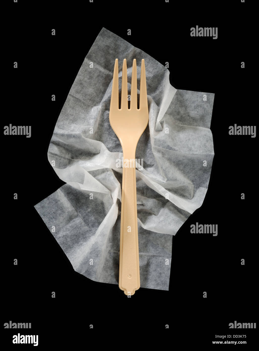 A plastic dinner fork on a crumpled cleaning napkin. - Stock Image