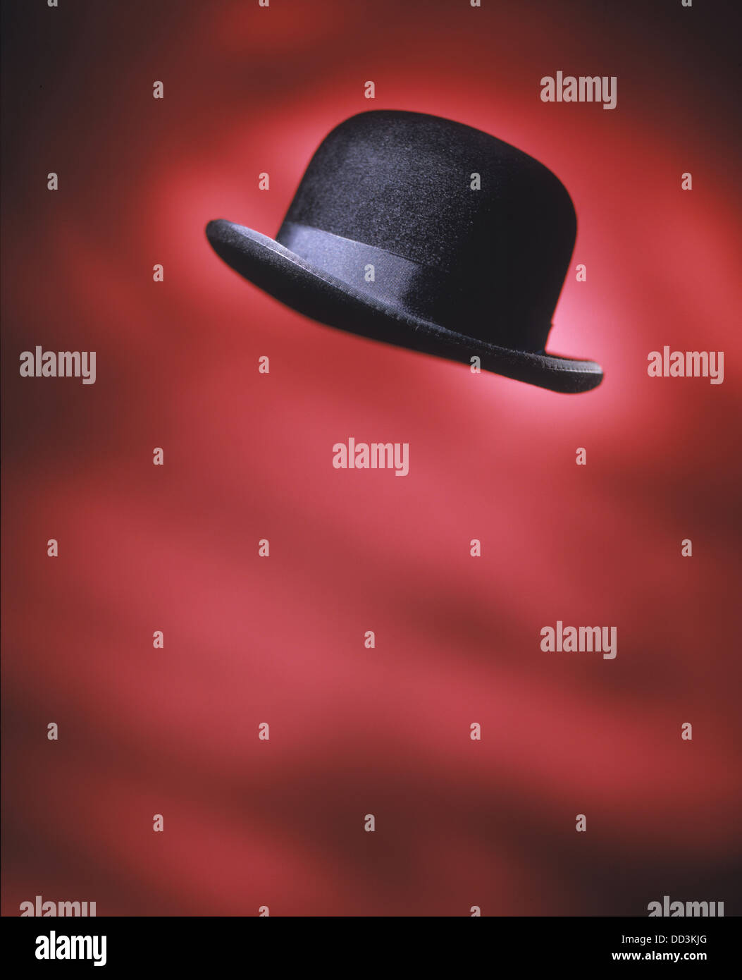 A black mens derby hat flying in the air. Bright red background - Stock Image