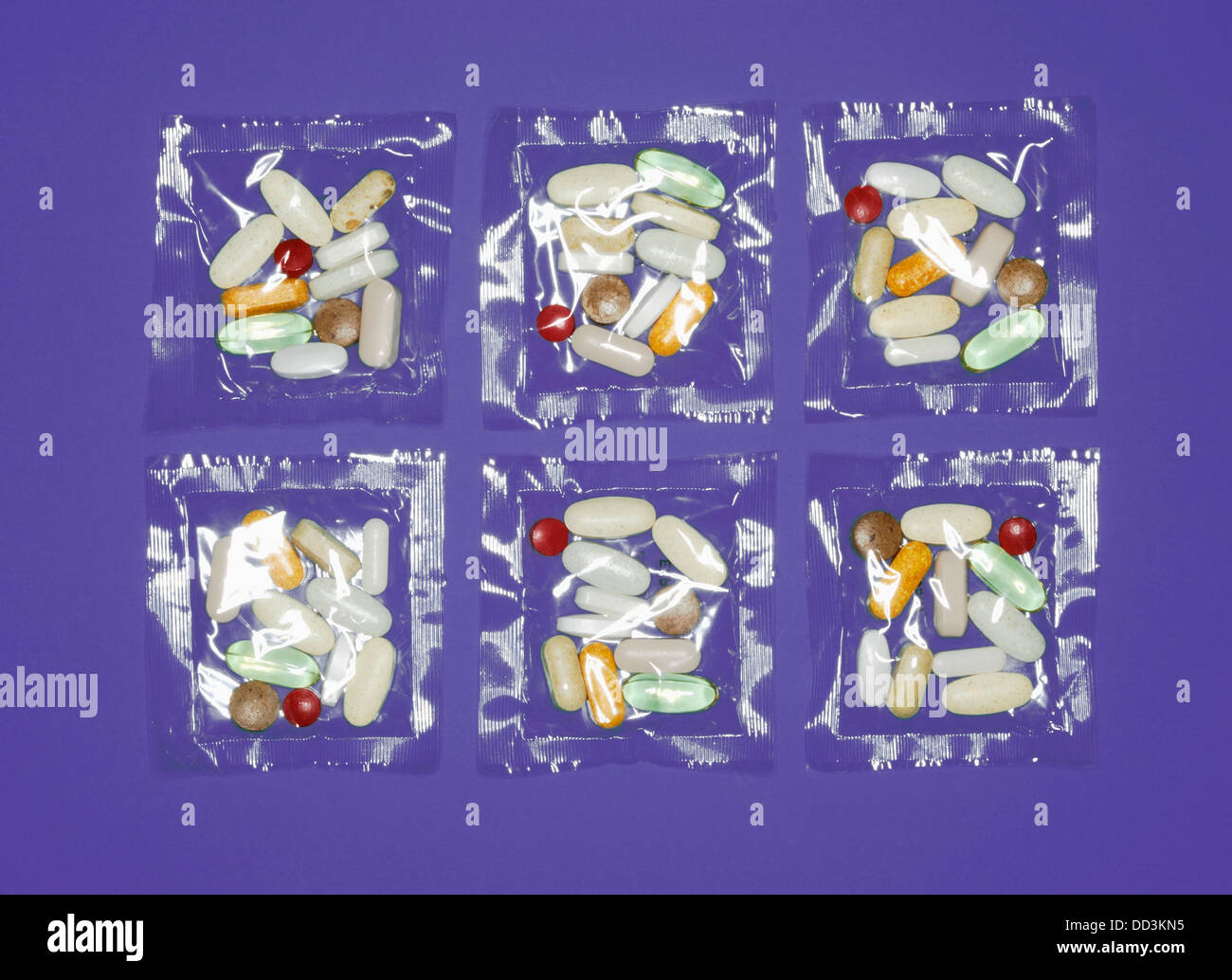 A plastic clear packets of vitamin supplements - pills, capsules and tablets. Blue background - Stock Image