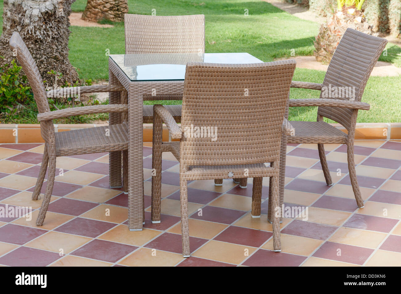 Cane Outdoor Patio Furniture With Glass Table And Chairs On Tiled Floor    Stock Image