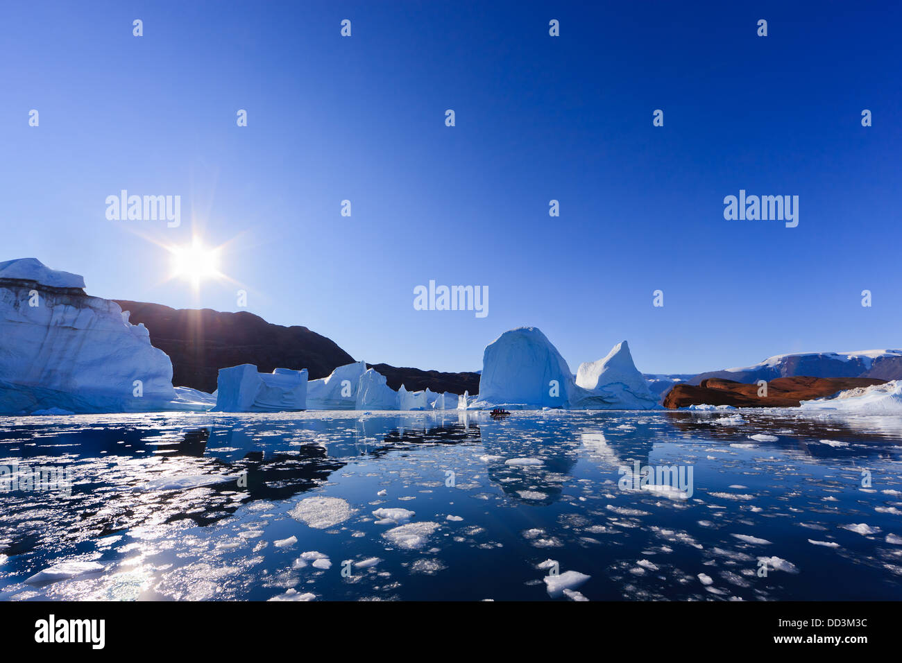 Cruising between the icebergs at Røde Ø, Scoresby sund, Greenland - Stock Image