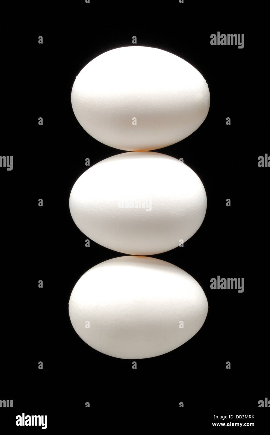 Three white whole chicken eggs together on a black background - Stock Image