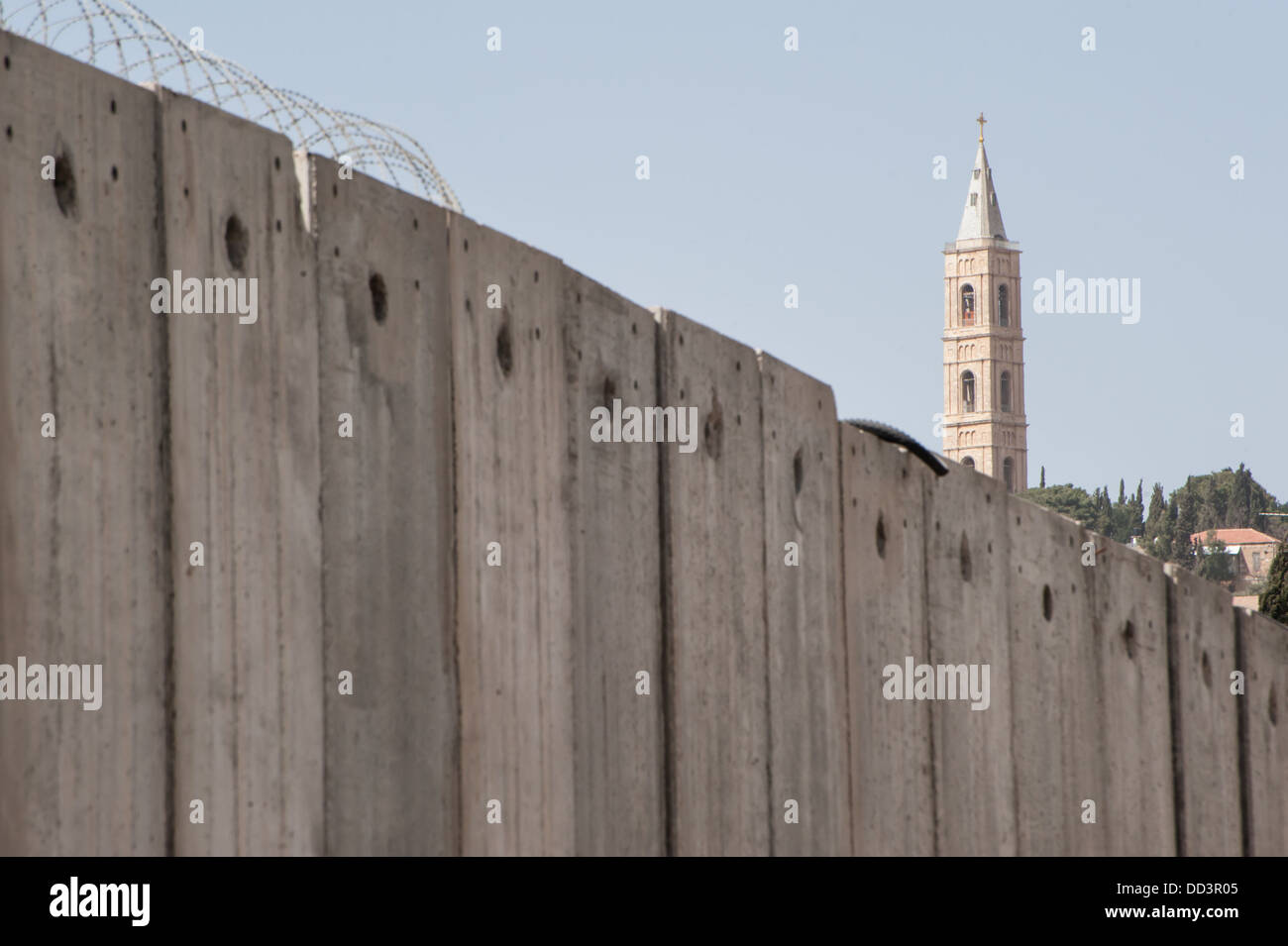 A church tower rises above the Israeli separation wall that divides Palestinian neighborhoods in East Jerusalem. - Stock Image