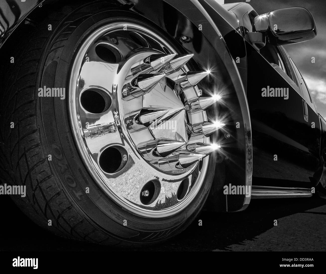 A spike tipped truck wheel at a custom car show - Stock Image