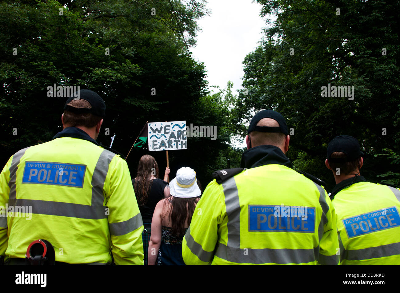 Balcombe protest against fracking. A man holds a placard saying 'We are earth' in front of a line of police. - Stock Image