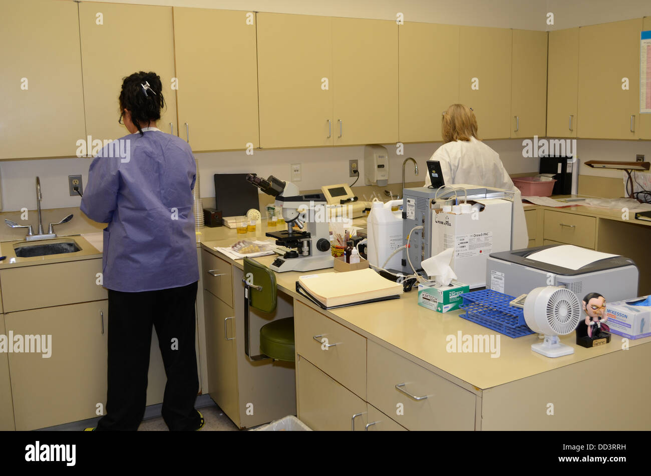 Female staff at work in prison laboratory testing samples from inmate for potential drug use. Intake process. - Stock Image