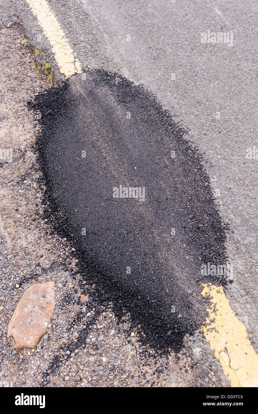 A piece of tarmac being used to fill potholes in the road - Stock Image