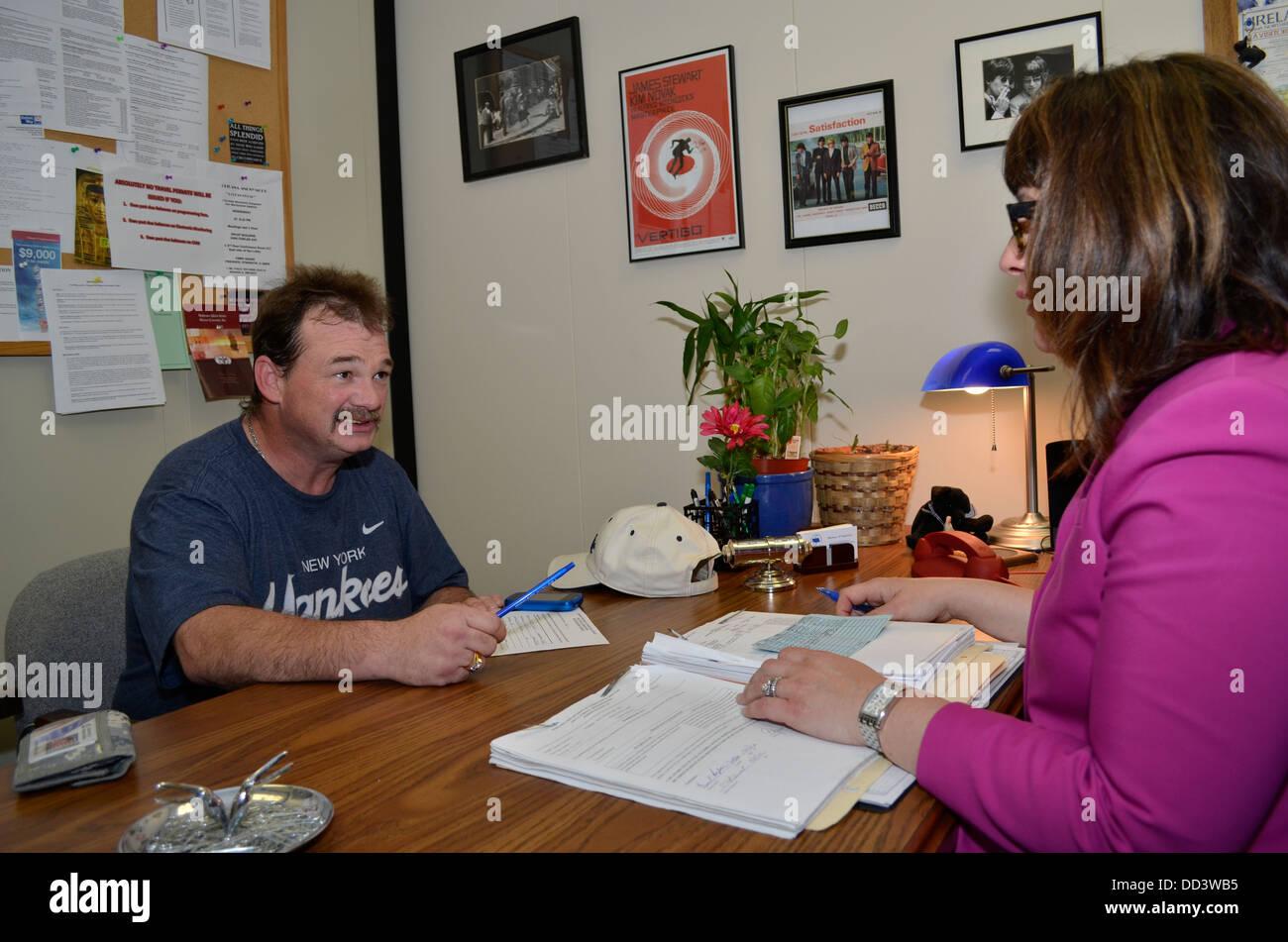 Male parolee meeting with female parole officer. Adult Parole in Omaha, Nebraska, USA. - Stock Image