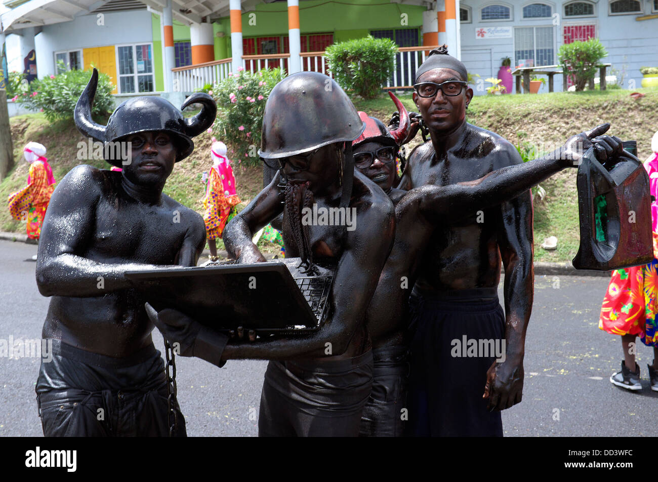 Grenada's Caribbean annual carnival Jab Jab revelers have painted their bodies black, put red helmets with make - Stock Image