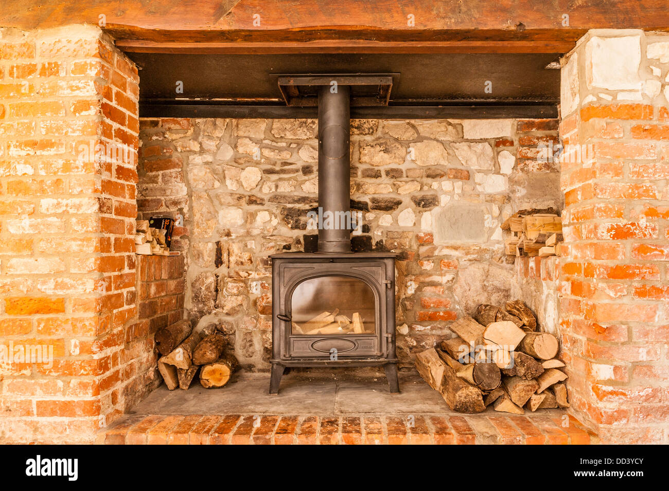 An inglenook fireplace with a woodburner - Stock Image