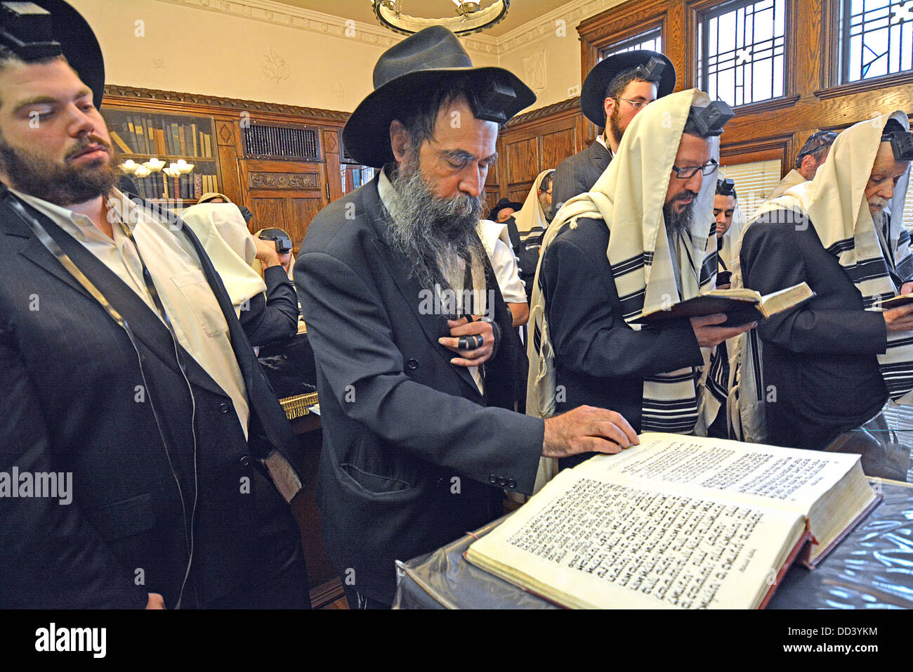 Religious Jewish men pray in the Rebbe's office at Lubavitch Headquarters in Brooklyn, New York. - Stock Image
