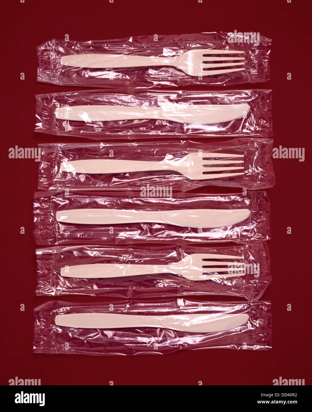 Plastic forks and knives in plastic bags - Stock Image
