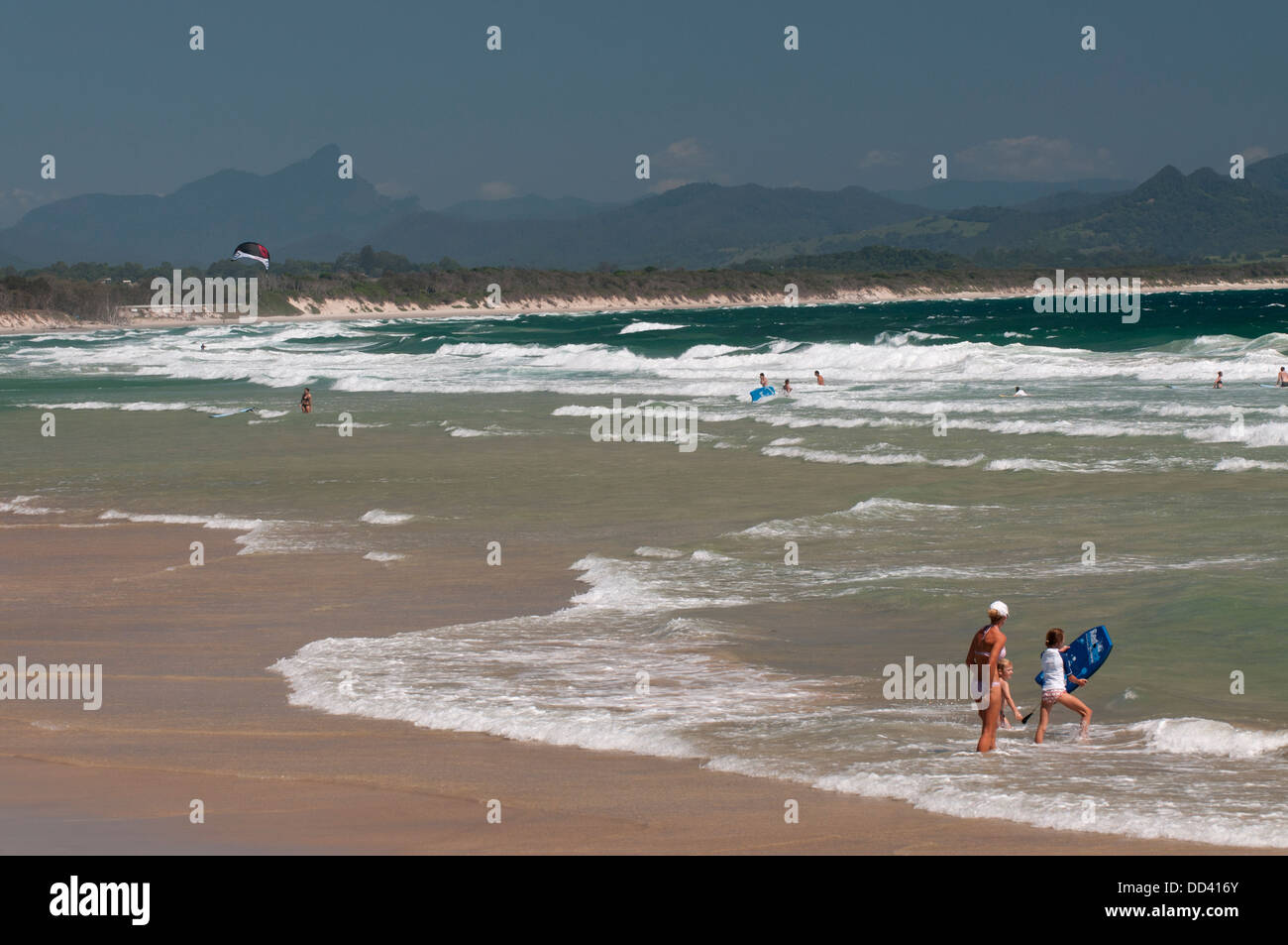 Family playing in the surf on Belongil Beach with Byron Bay's hinterland and Mt Warning beyond. - Stock Image