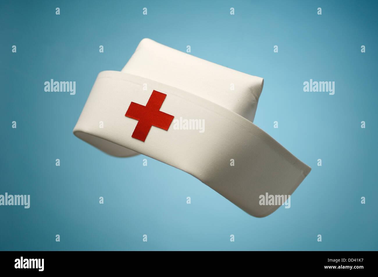 A hospital nurse hat floating on a blue background. - Stock Image