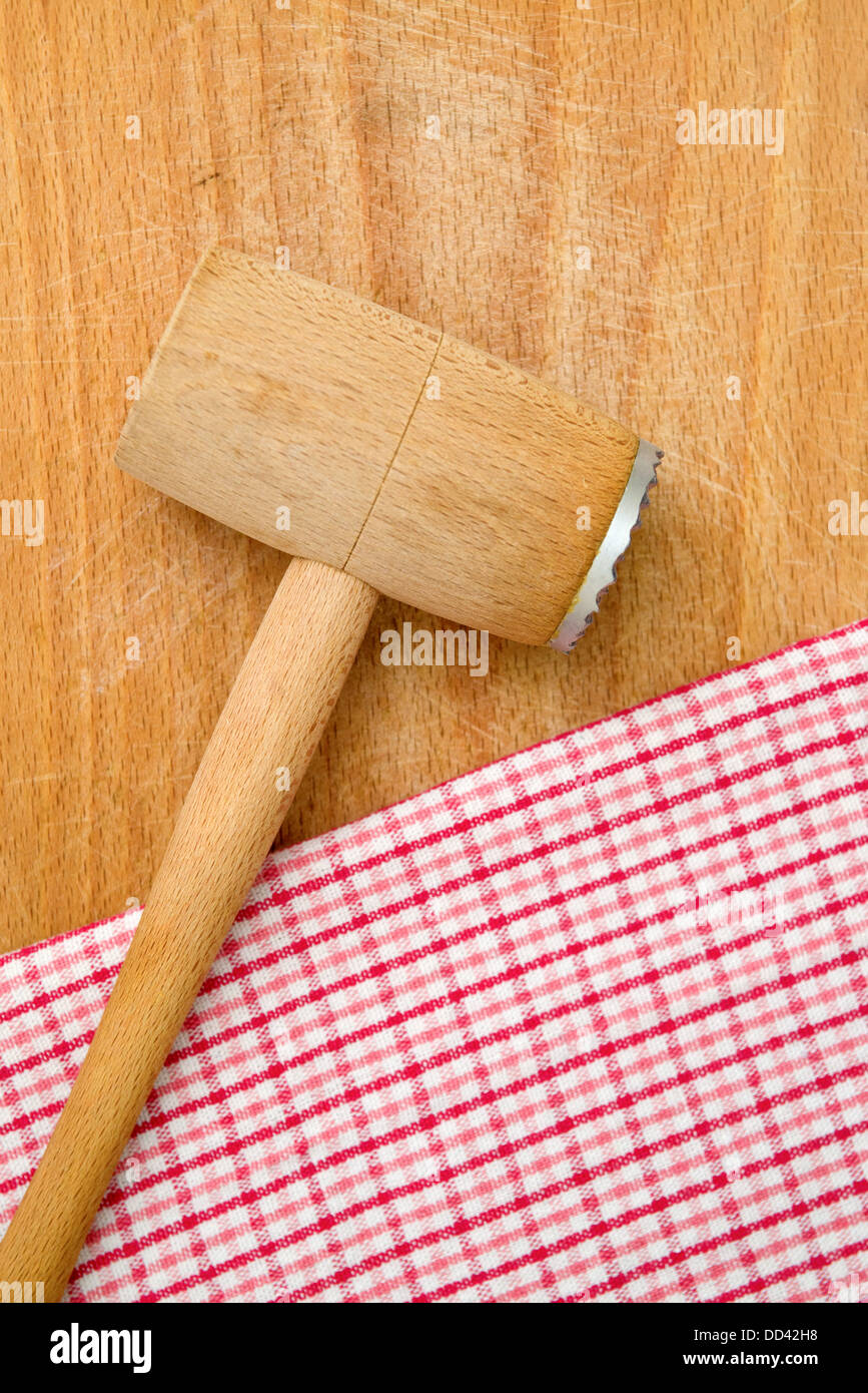 Meat Tenderizer On Wooden Kitchen Table, Checkered Table Napkin In  Background.