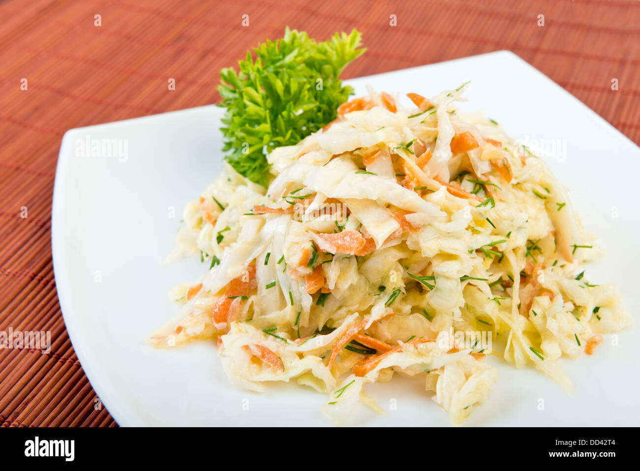 Low fat vegetable salad coleslaw (cabbage, carrot, dill, mayonnaise) on plate at restaurant table - Stock Image