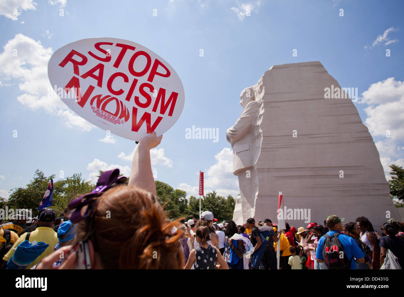 Woman holding up 'Stop Racism Now' sign at the MLK memorial - Washington DC - Stock Image