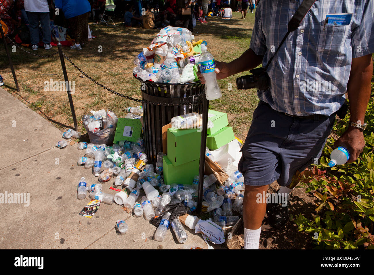 Discarded plastic water bottles overflowing from waste bin - Stock Image
