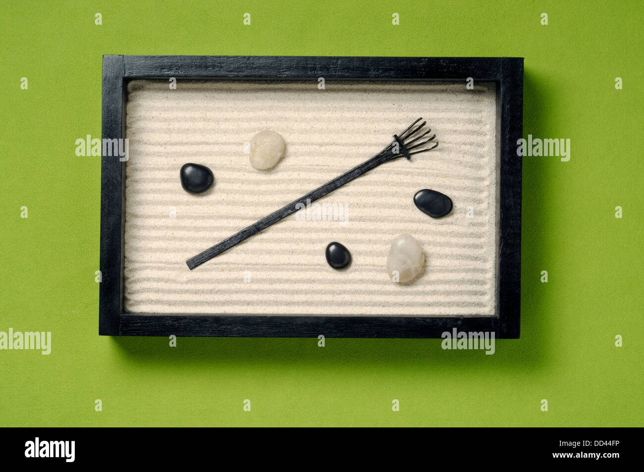 A small rectangular sand zen garden with rocks and a small rake. - Stock Image