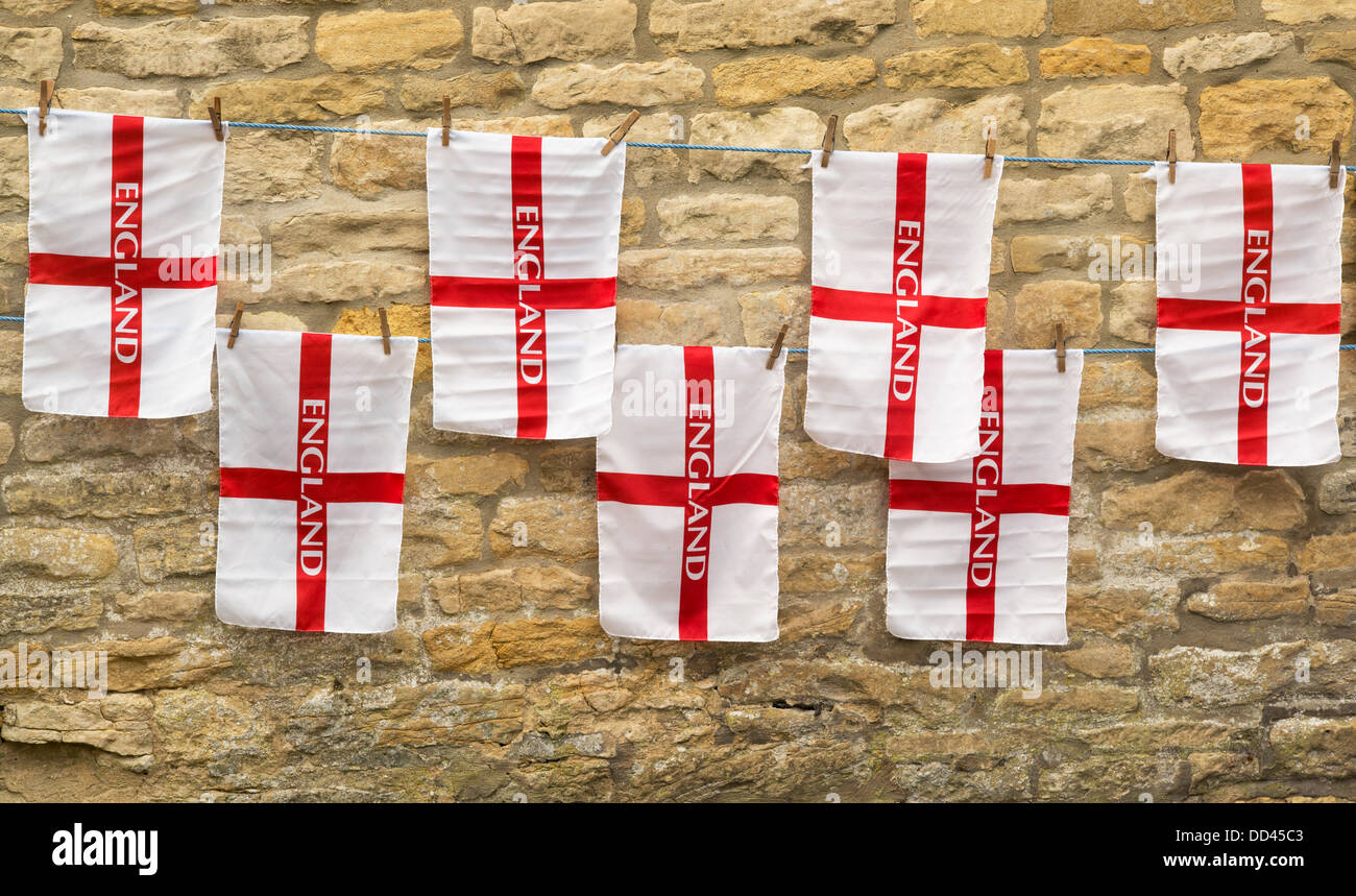 England flags pegged on lines against a cotswold stone wall. Cotswolds, UK - Stock Image