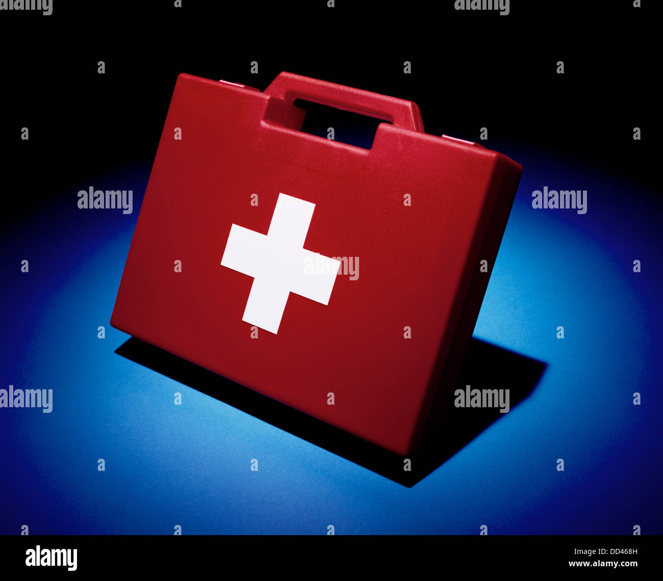 A bright red first aid box spot lit of a blue background - Stock Image