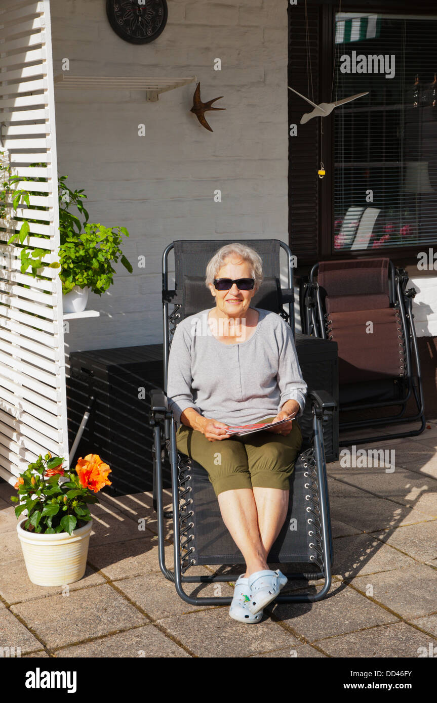 woman in her 70s in her garden reading magazines happy on summer day western Finland northern Europe - Stock Image