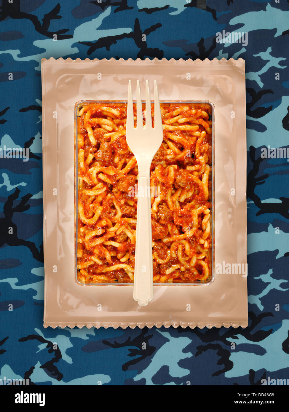 Military food rations or MRE Meals Ready to Eat on a camouflaged background. Packages open with plastic utensils. - Stock Image