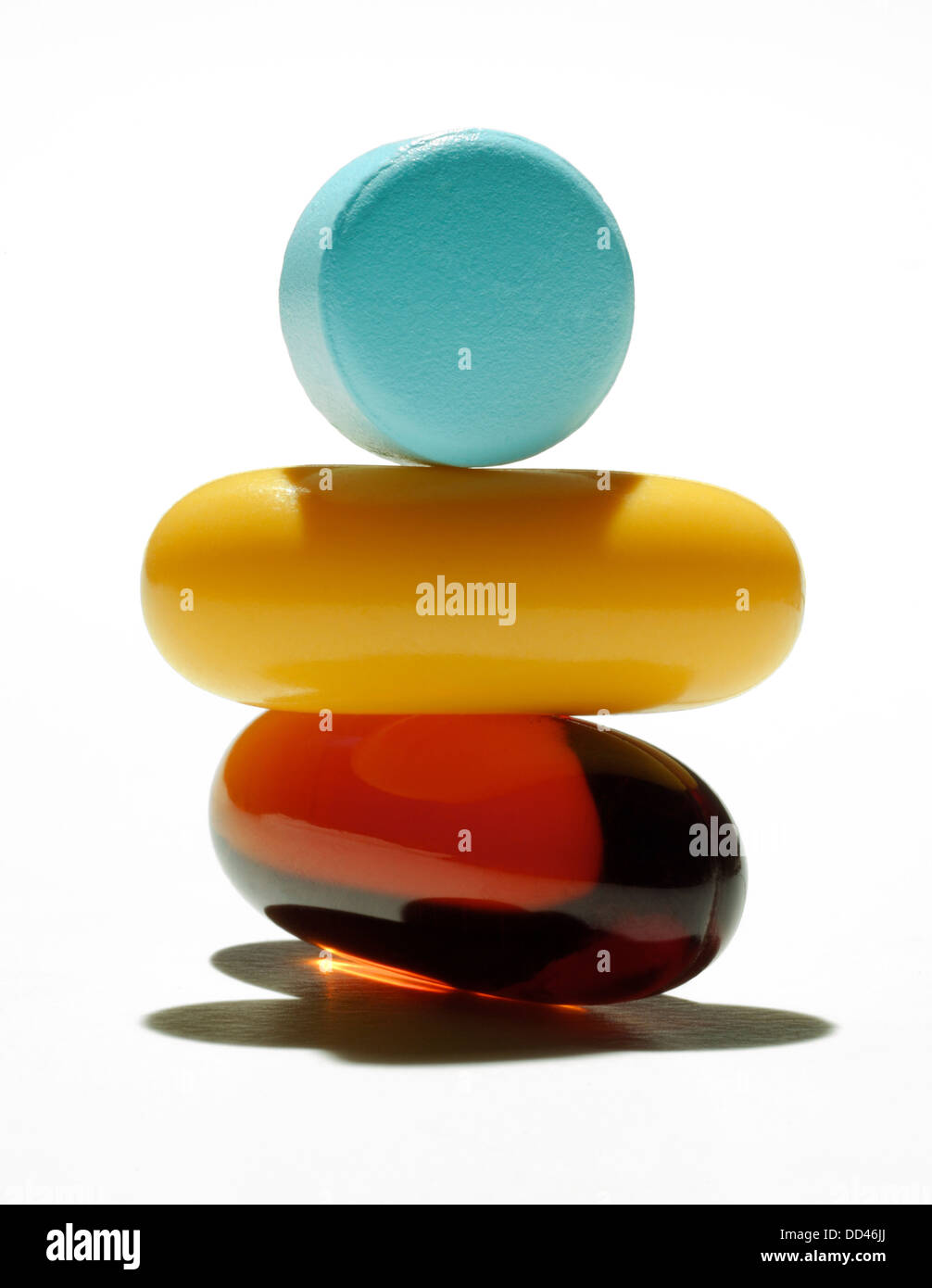 A balance stack of a vitamin capsule, pill and tablet. White background - Stock Image