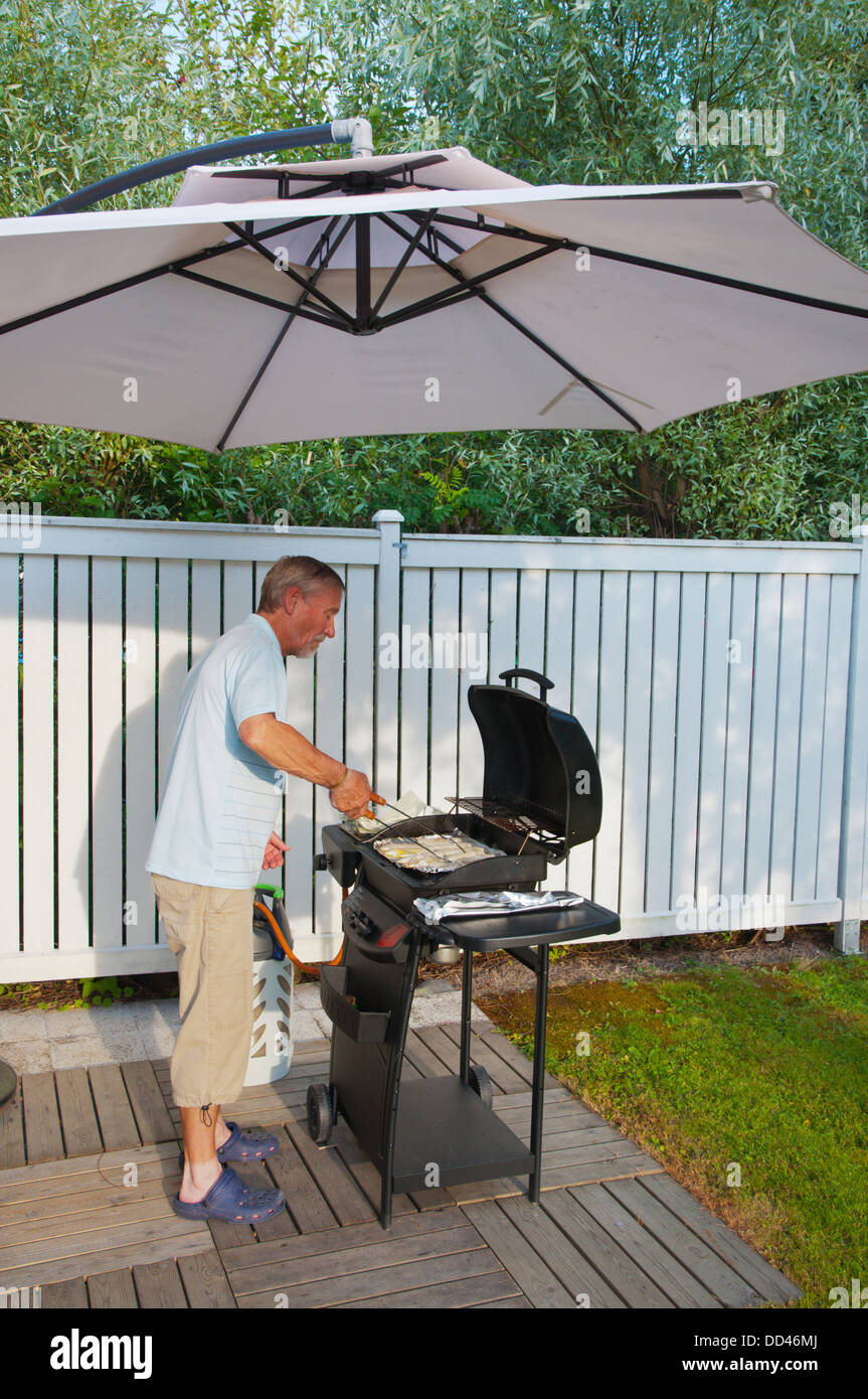 Man in his 70s grilling fish in garden western Finland northern Europe - Stock Image
