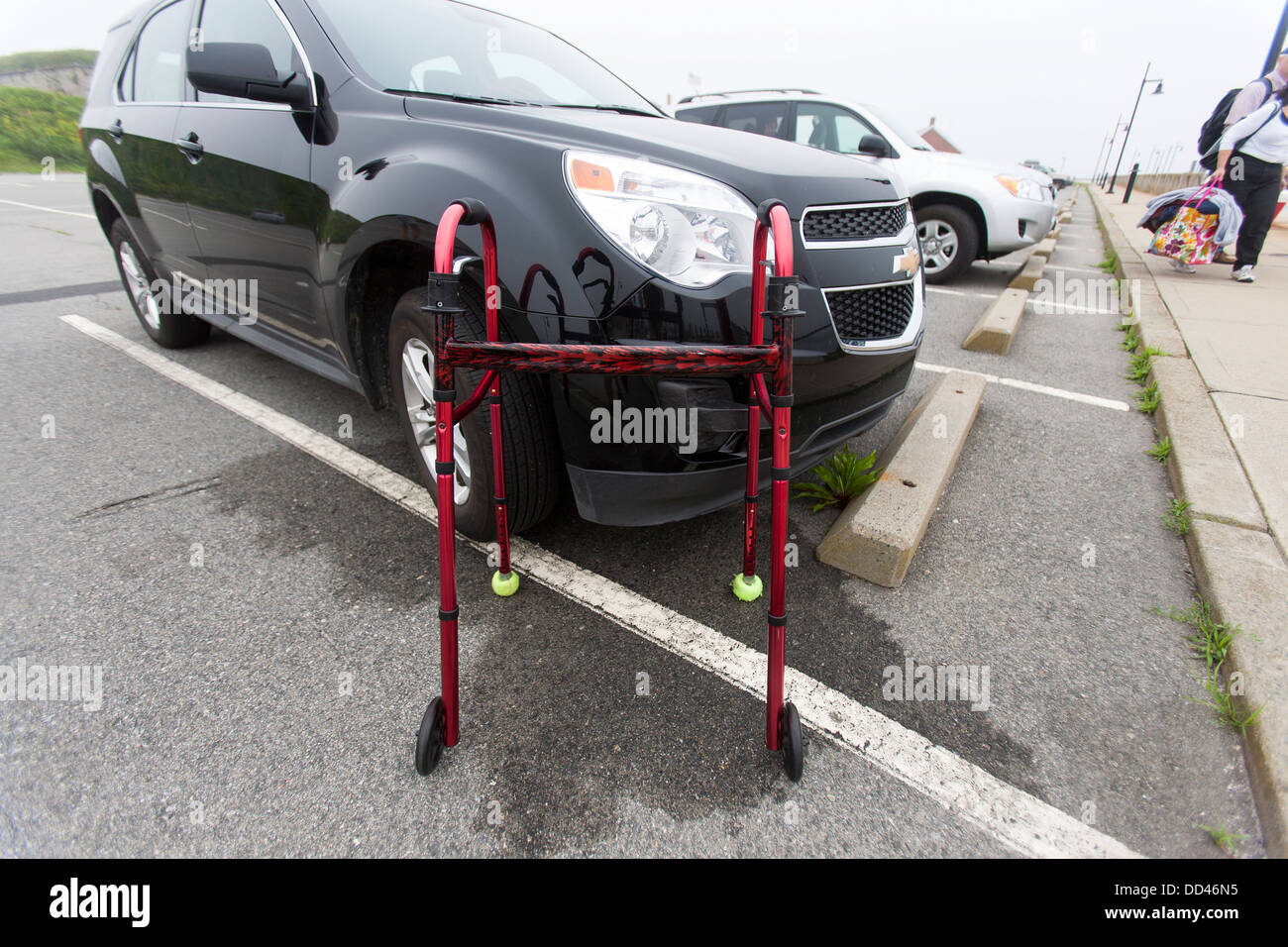 A zimmer frame walker walking aid in a parking lot at a disabled ...