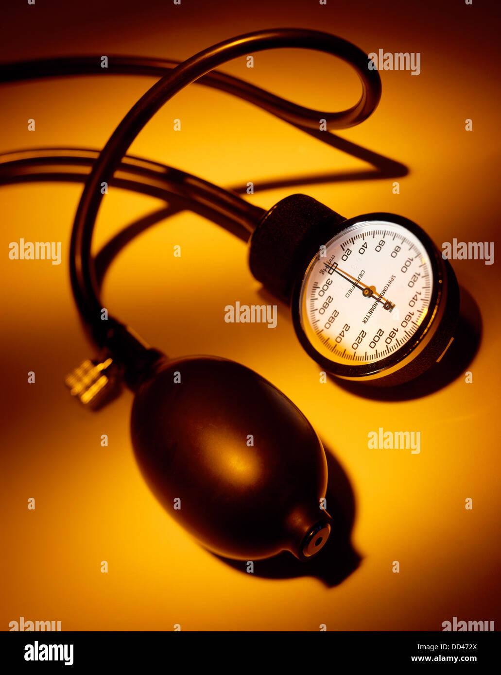 A blood pressure gauge on a orange background - Stock Image