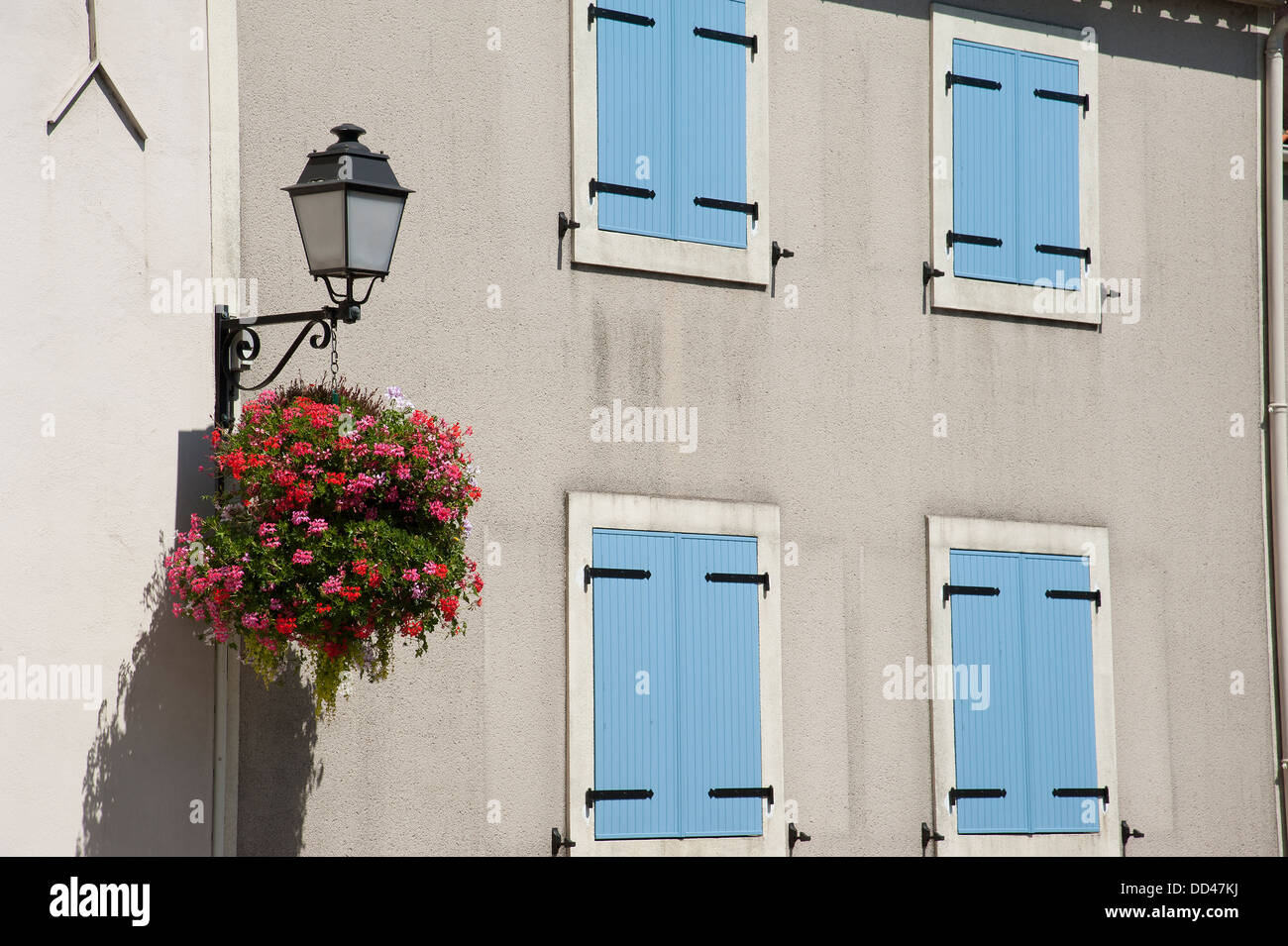 Hanging basket of flowers and shuttered windows A traditional French country home - Stock Image