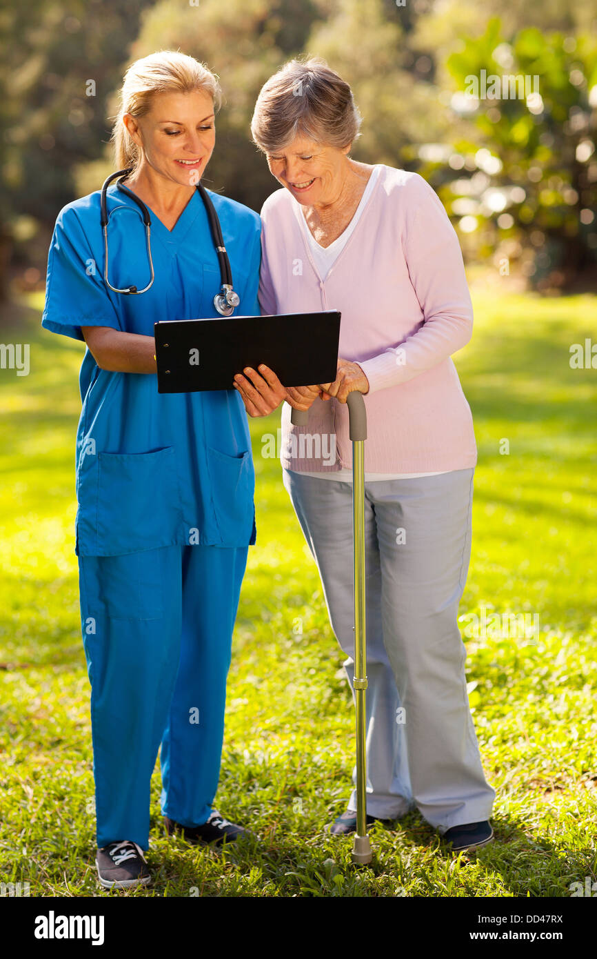 smiling nurse showing senior patient her medical test results outdoors - Stock Image