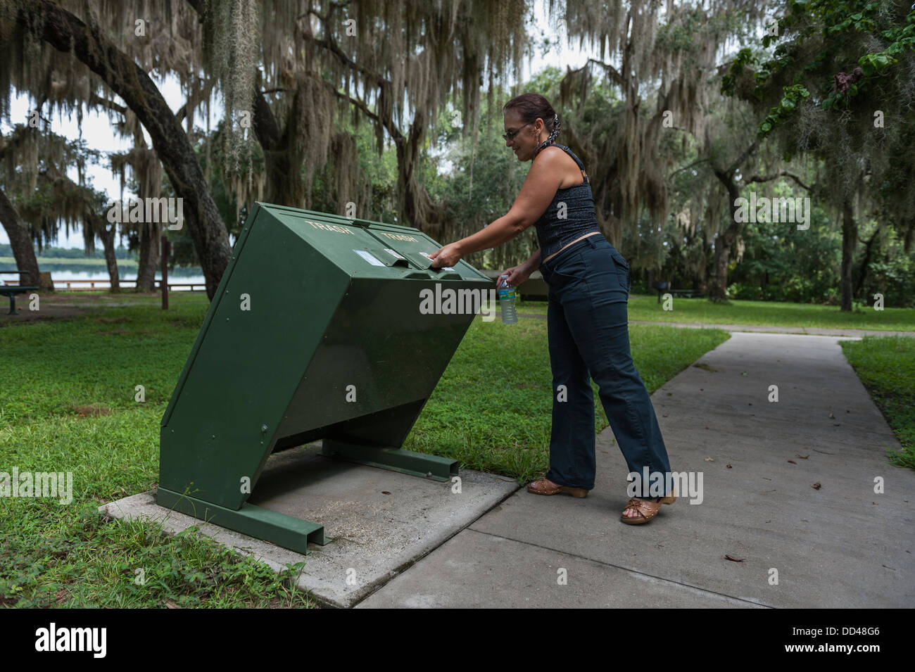 A woman discarding trash while at the Mill Dam State Park Ocala, Florida National Forest USA - Stock Image