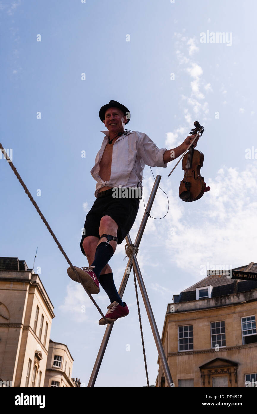 A tightrope walker busking playing a violin in Bath , Somerset , England , Britain , Uk - Stock Image