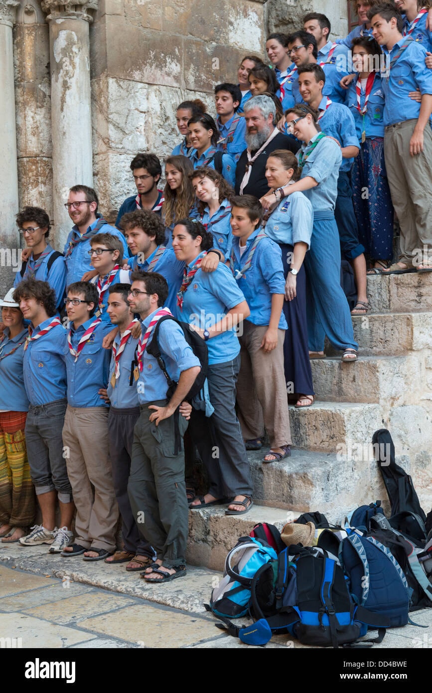 Group of scouts in uniforms pausing on the steps of the Holy Sepulcher. Jerusalem Old City. Israel. - Stock Image
