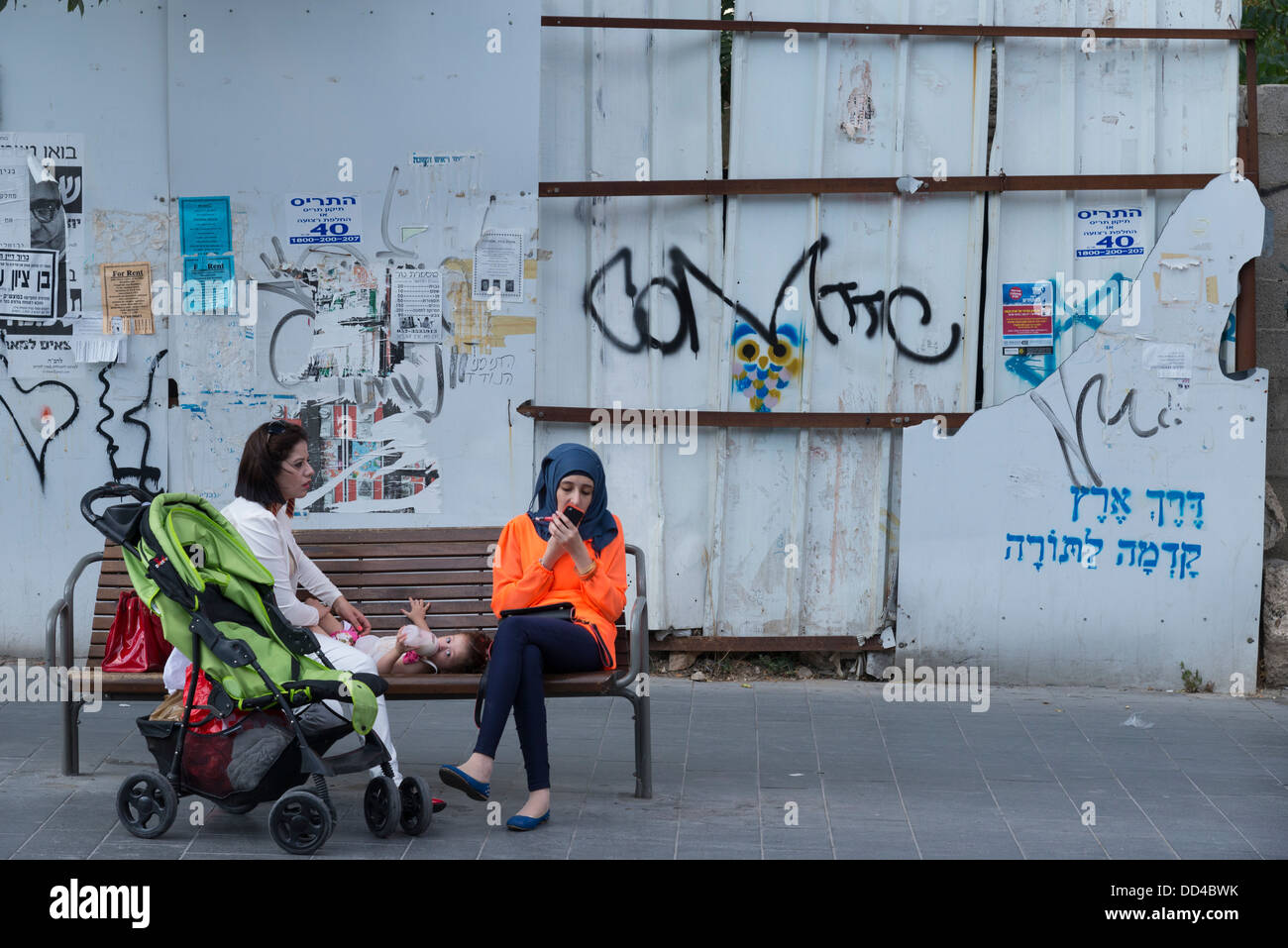 Two Palestinian women and baby resting on a bench with building site and graffiti in background. Jaffa Street. Jerusalem. - Stock Image