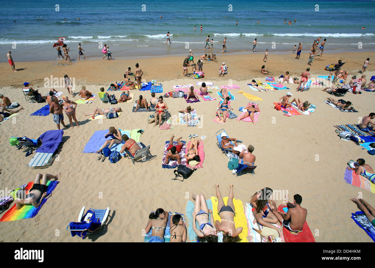 Crowded city beach during a hot summer day in Gijon, north Spain - Stock Image