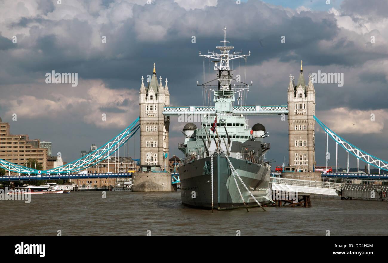 Tower Bridge London with HMS Belfast ship under a dramatic sky Summer 2013 Stock Photo