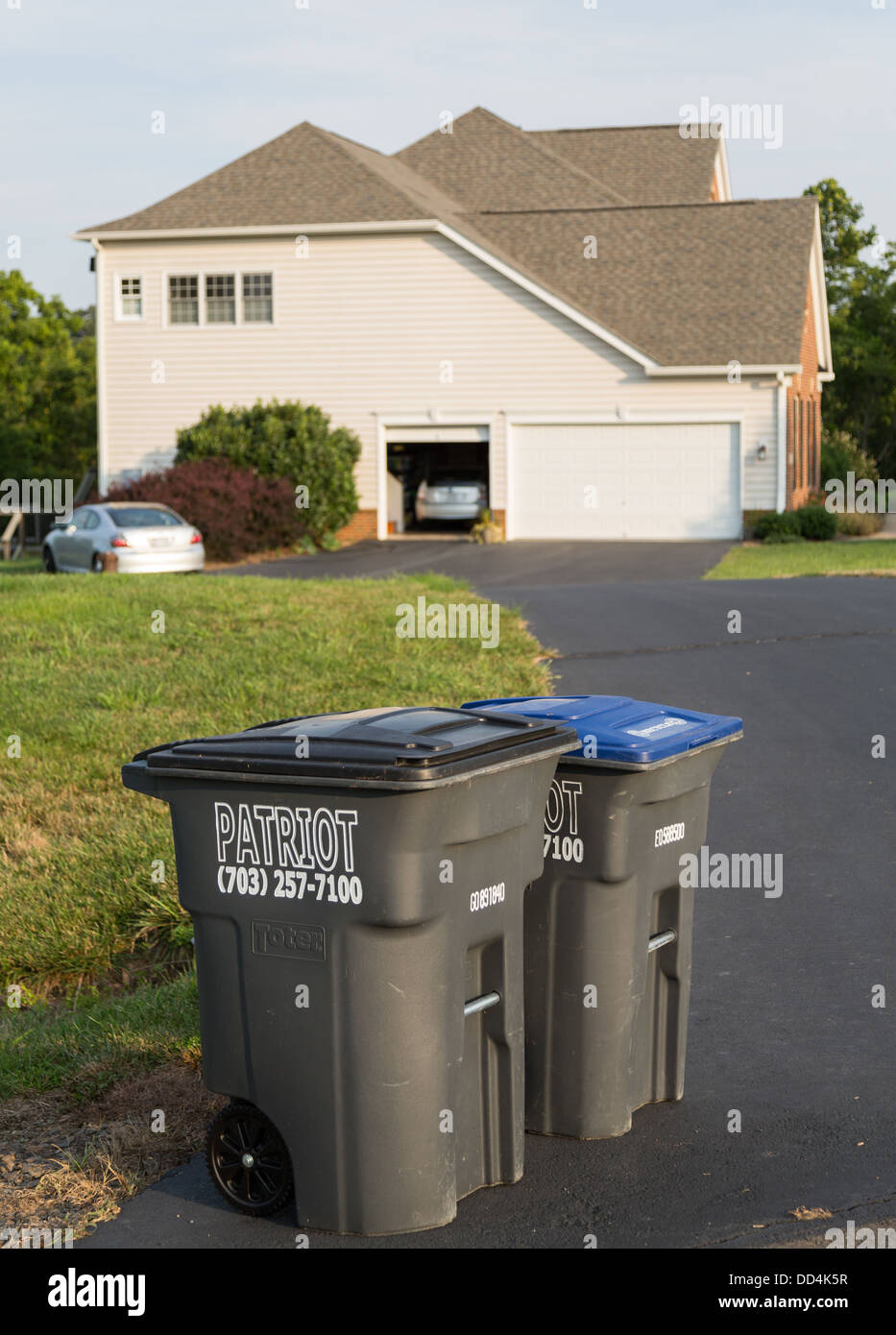 Typical US trash cans for rubbish collection outside single family home in suburbs of Virginia USA - Stock Image