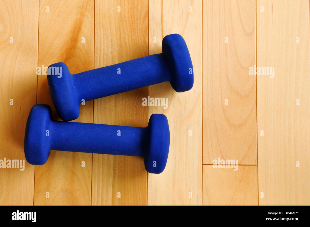 Blue Weights on Hardwood Floor of Fitness Center, view from above, copy space - Stock Image
