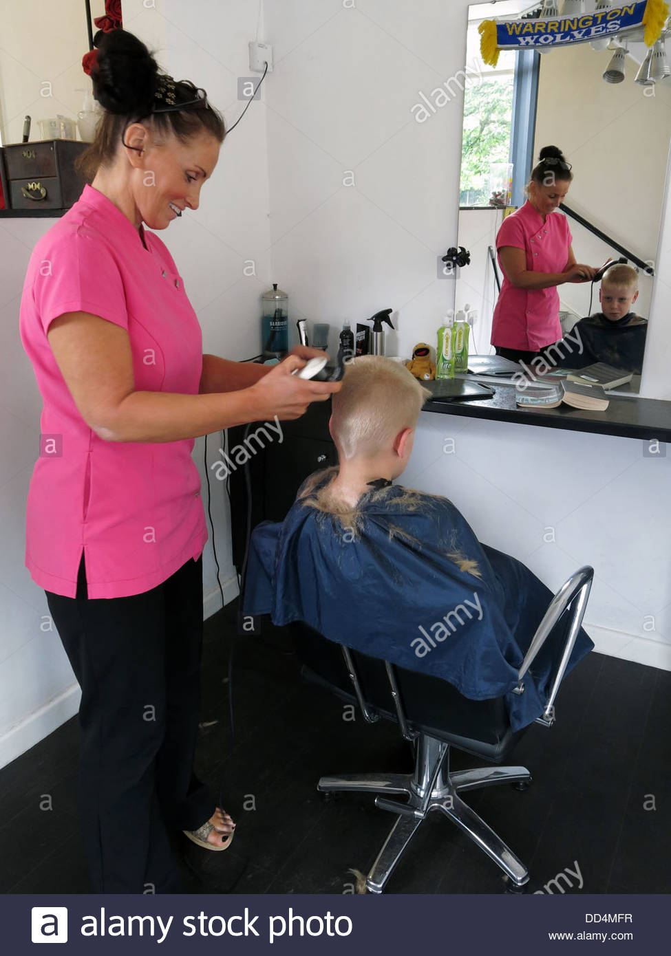 Young boy having a haircut at a traditional barber shop, Latchford, , Warrington, Cheshire, North West England, - Stock Image