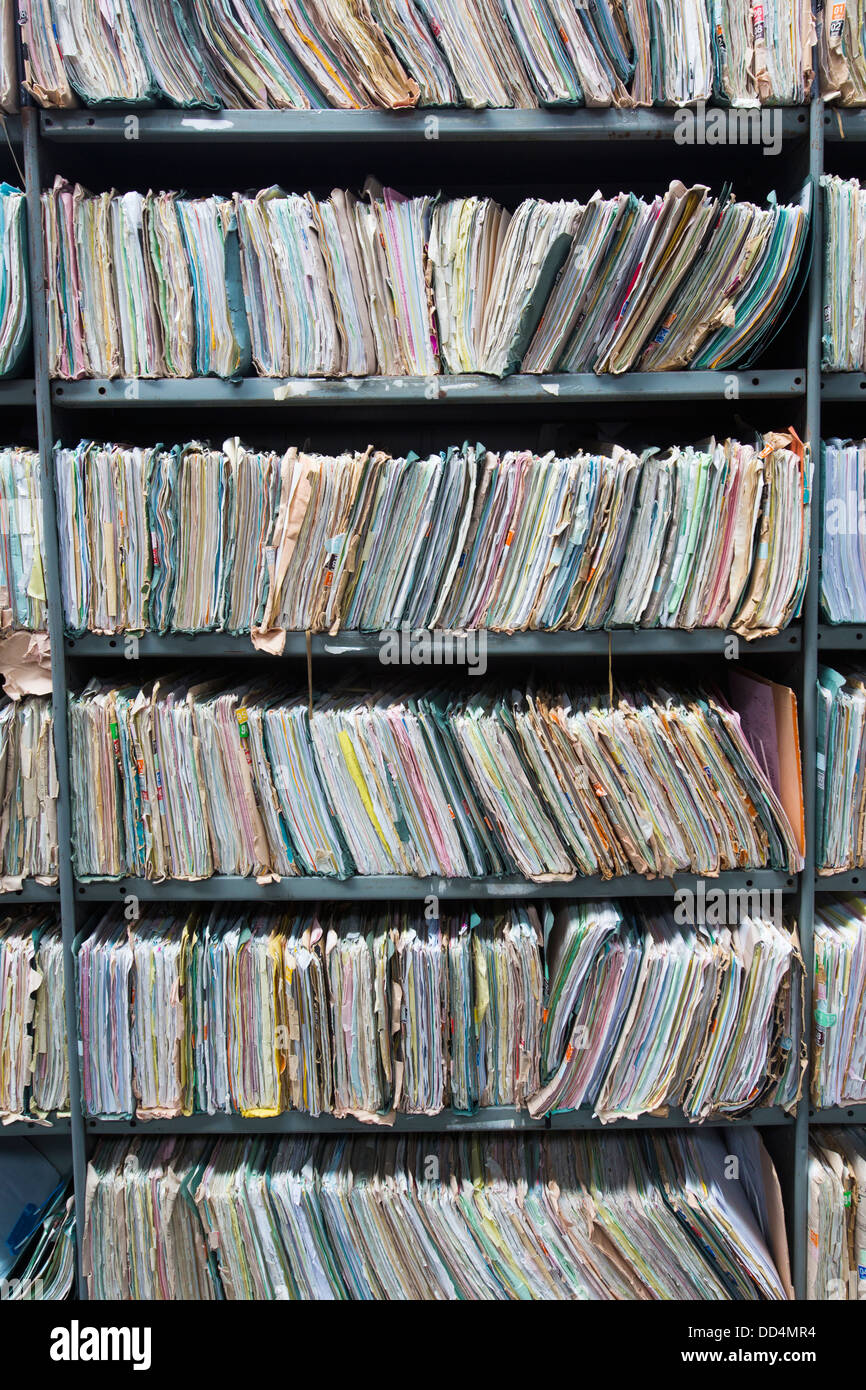 Shelves in a warehouse stuffed with office paperwork, folders and files which have now been transcribed on to digital - Stock Image