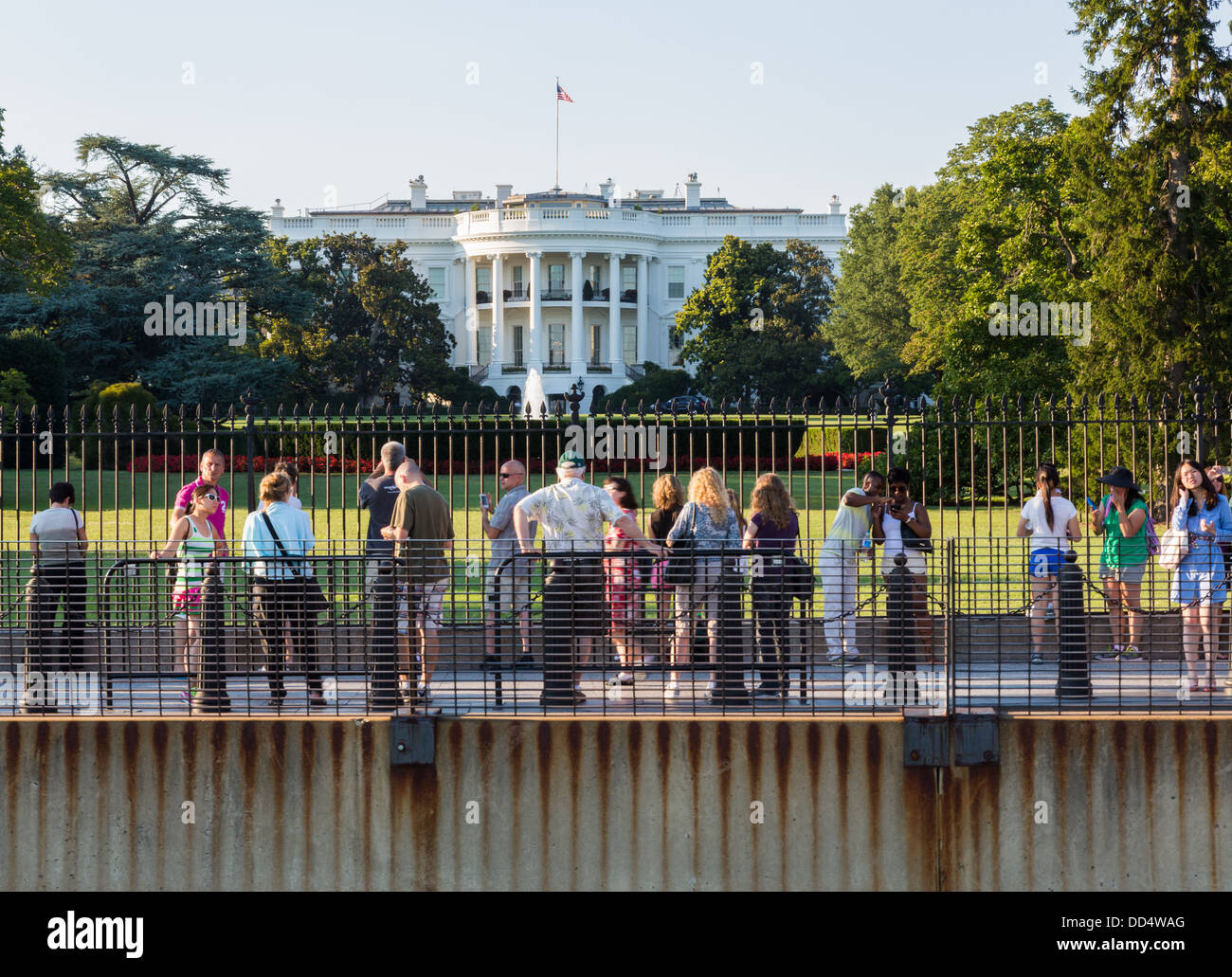 Crowds look at South Lawn view of White House Washington DC by fence and security barriers - Stock Image