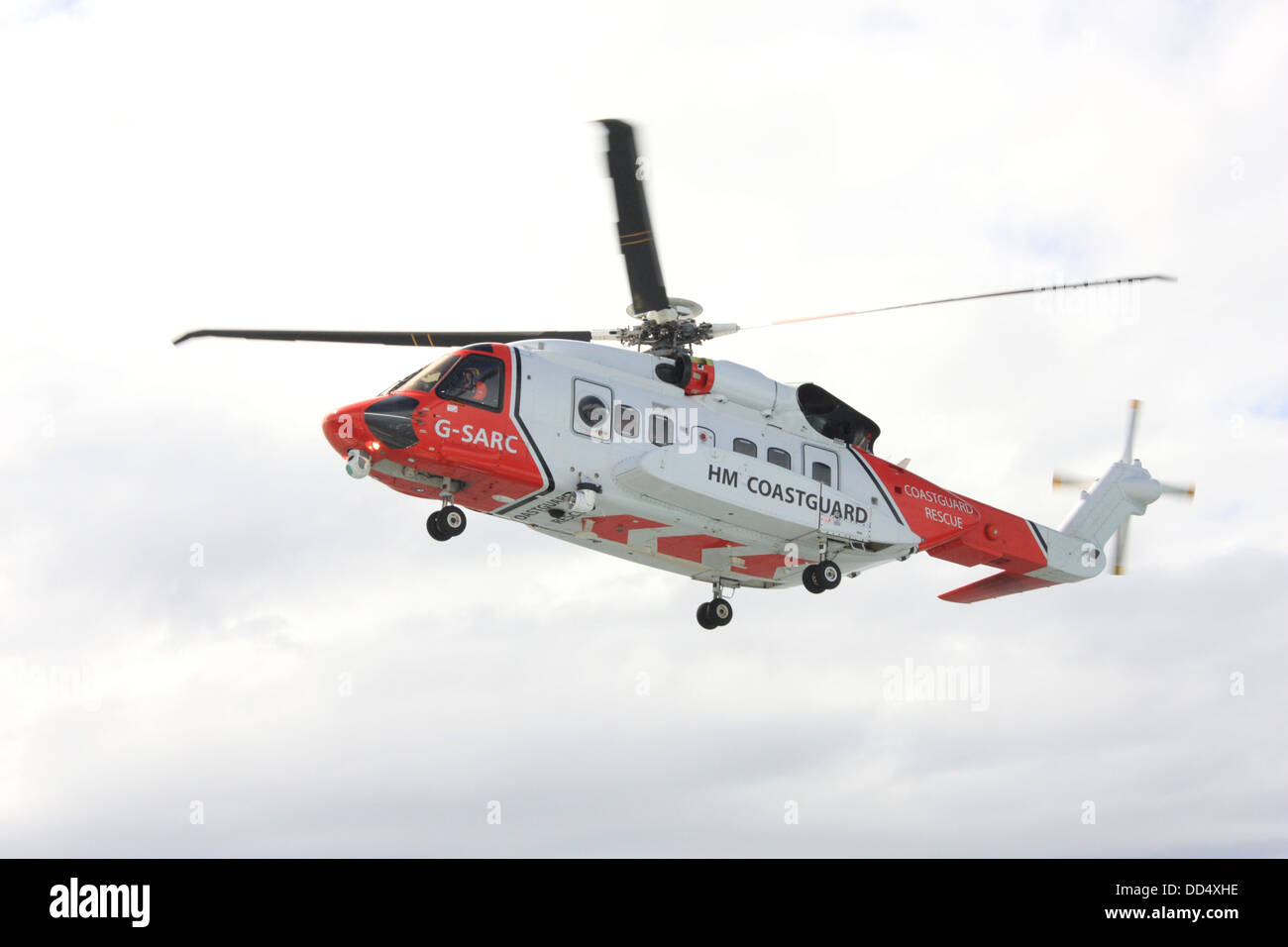 Coastguard search and rescue helicopter on exercise winching a crewman onto a ferry in the Minch near the Outer - Stock Image