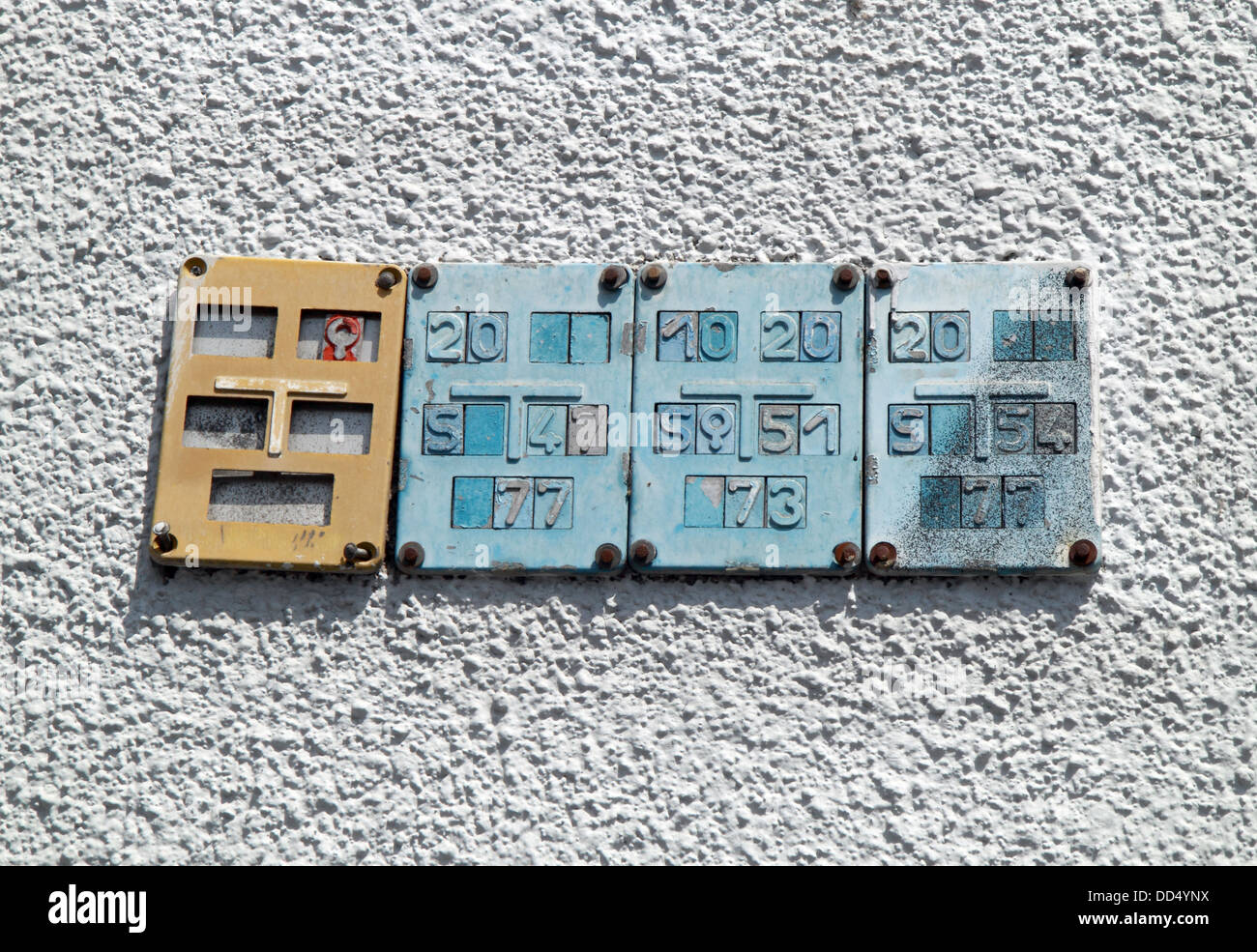 3 blue and one beige iron plates with numbers on, mounted on the outside of a house wall. - Stock Image